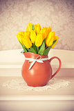 Bunch yellow tulips in jug on wooden table