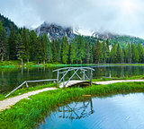 Alpine summer lake and sunshine through cloudy sky
