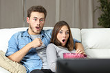 Amazed couple watching tv at home