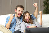 Euphoric couple watching tv at home