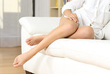 Woman waxed legs resting on a couch