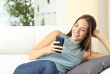 Happy housewife using a mobile phone on a couch