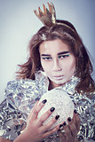Portrait of pretty woman wrapped in foil with coronet looking forward standing on light grey background