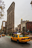Yellow taxi and Flatiron building at Fifth Avenue av in Manhattan
