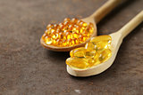 food supplement of fish oil capsules in a wooden spoon - healthy food
