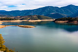 Ladonas artificial lake in Greece against a blue sky with clouds, and mountains as background