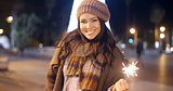 Pretty young woman celebrating with a sparkler