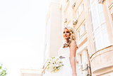 Beautiful bride in magnificent dress stands alone on stairs