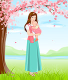 Mom holding baby in sling. Young mother under blossoming tree