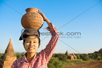 Asian traditional female farmer carrying clay pot on head