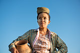 Mature Asian traditional female farmer carrying clay pot