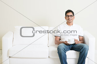 Asian man sitting on couch and drinking coffee