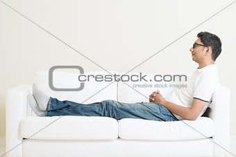 Asian man resting and daydream on couch