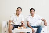 Men friends watching sport match on tv