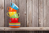 Colorful coffee cups on shelf