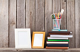 Wooden shelf with photo frames, books and supplies