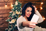 people, holidays and technology concept - beautiful brunette woman in white  sweater taking selfie picture by smartphone over christmas tree and living room background
