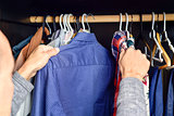 young man choosing a shirt from a clothes rack