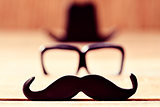 mustache, eyeglasses and hat forming the face of a man