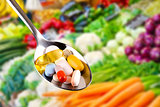spoon with pills, dietary supplements on vegetables background