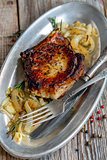 Pork chop with rosemary and fried onions.