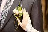 hang of a bride adjusting boutonniere on grooms jacket