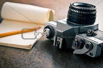 old analogue camera and notepad