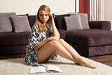 girl in home sitting on carpet and reading