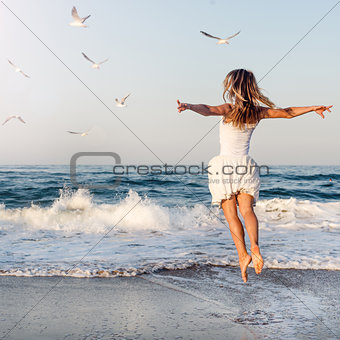Beautiful girl  jumping on sea