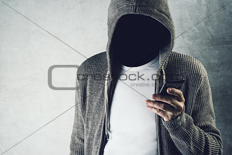 Faceless hooded person using mobile phone, identity theft concep