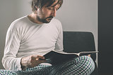 Man reading magazine early in the morning, wearing pajamas