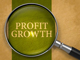 Profit Growth through Loupe on Old Paper.