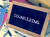 Handwritten Downsizing on a Chalkboard.