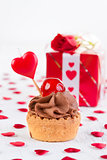 cup-cake with cherry in front of gift box