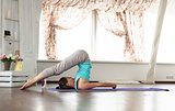 young beautiful girl practicing yoga at home.