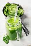 Healthy green smoothie with straw in a jar mug