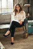 Photo of stylish brunet woman sitting on coach in loft room
