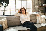 Concentrated stylish woman is sitting on couch in loft room