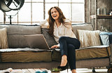 Photo of happy woman sitting on couch in front of open laptop