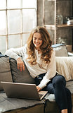 Smiling elegant woman sitting on couch and working on laptop