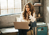 Stylish brunet woman sitting on couch and working on laptop