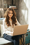 Elegant dressed brunet woman working on laptop in loft apartment