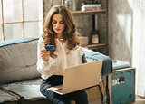 Elegant dressed woman on couch typing info from credit card