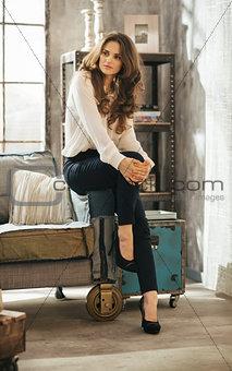 Portrait of beautiful woman in elegant clothing sitting in loft