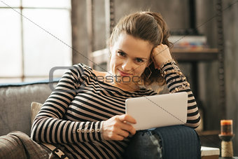 Portrait of young woman is laying on couch and holding tablet