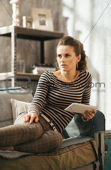 Thoughtful young woman is sitting on couch and holding tablet