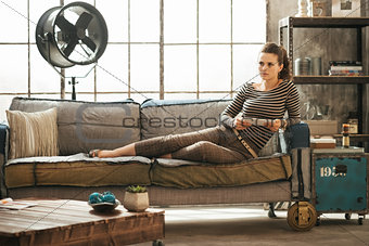 Thoughtful stylish woman is sitting on couch and holding tablet