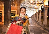 Woman with shopping bags standing under Christmas light, Venice