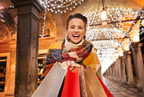 Excited woman with shopping bags standing under Christmas light