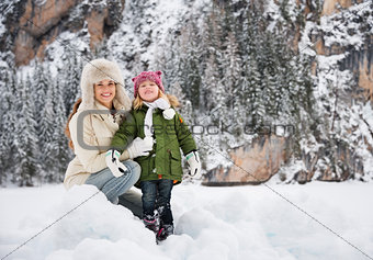 Portrait of happy mother and child in front of snowy mountains